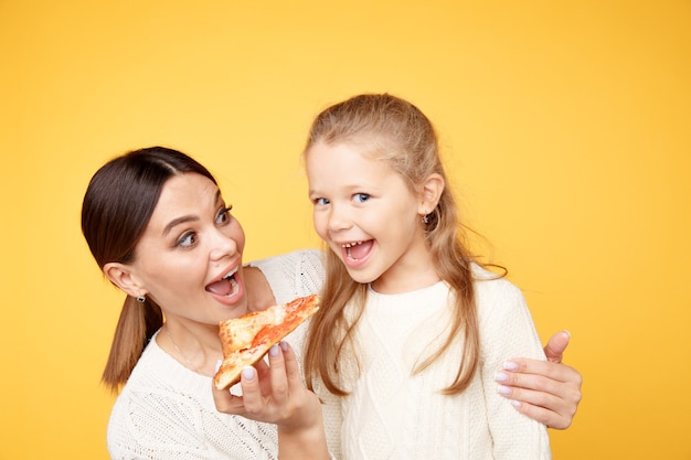 Mother and daughter eating pizza together and having fun isolated over the yellow studio