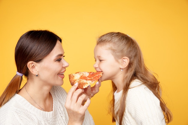 Mother and daughter eating pizza together