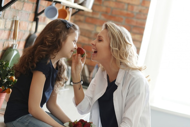 Mother and daughter eating strawberries in the kitchen