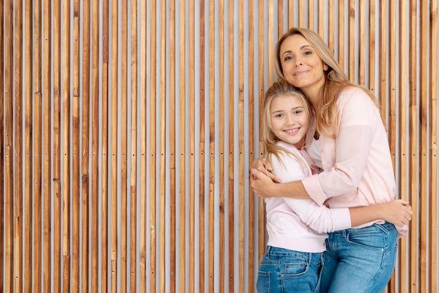 Mother and daughter embracing next to wooden background