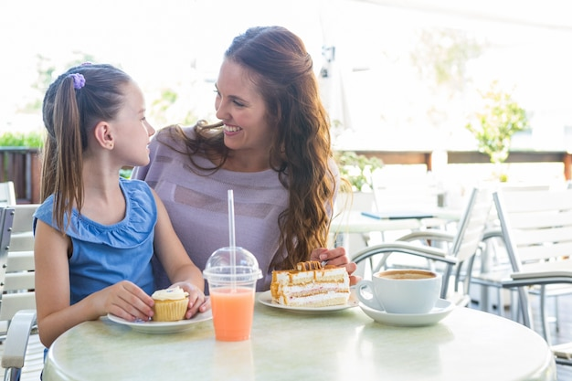 Mother and daughter enjoying cakes at cafe terrace