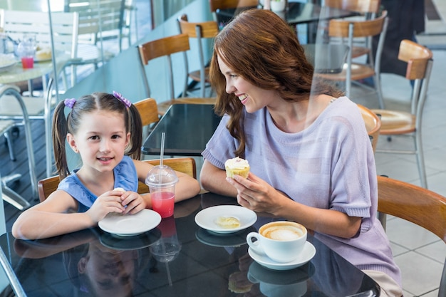 Mother and daughter enjoying cakes