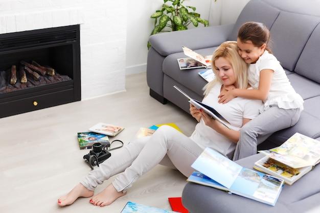 Mother and daughter enjoying photo album in livingroom