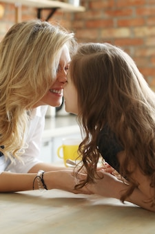 Mother and daughter eskimo kiss, also called kunik, nose kiss, or nose rub