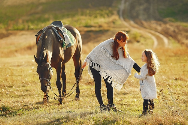 Mother and daughter in a field playing with a horse