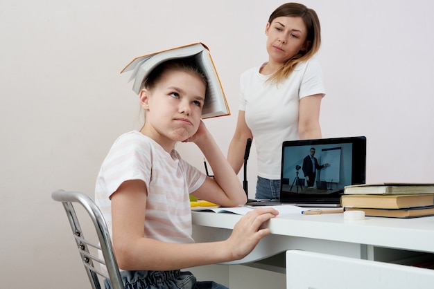 Mother and daughter fighting about homework, upset mother is angry to little bored daughter, homeschooling, misunderstanding