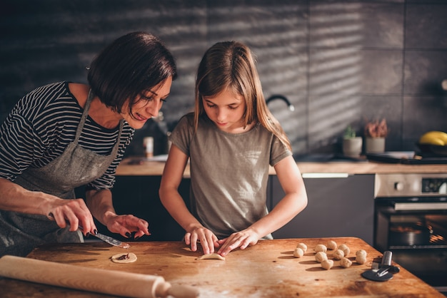 Mother and daughter filling ravioli with chocolate cream