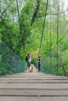 Mother and daughter in the forest walking over wooden bridge