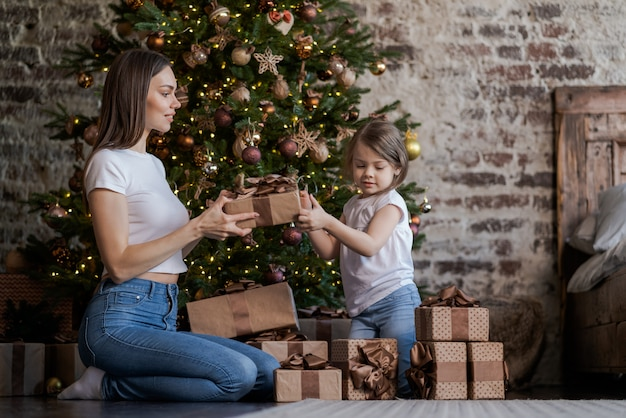 Mother and daughter in front of christmas tree, opening presents