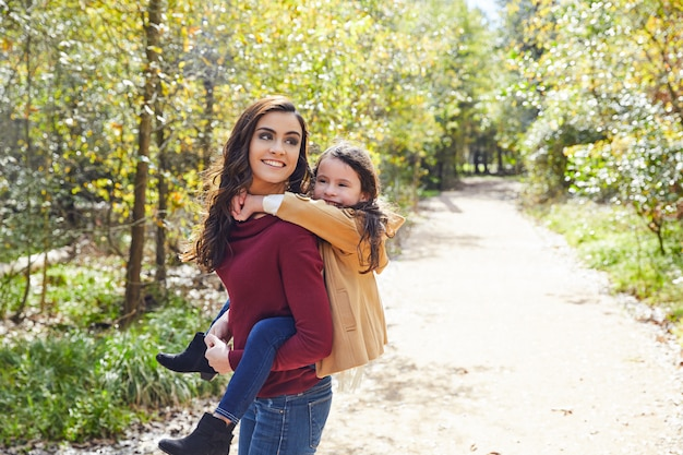 Mother and daughter fun piggyback in a park