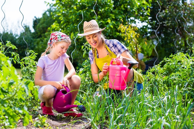 Mother and daughter gardening in garden