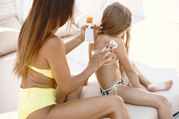 Mother and daughter going to sunbathe. parent applying sunscreen on chils, sitting by poolside.