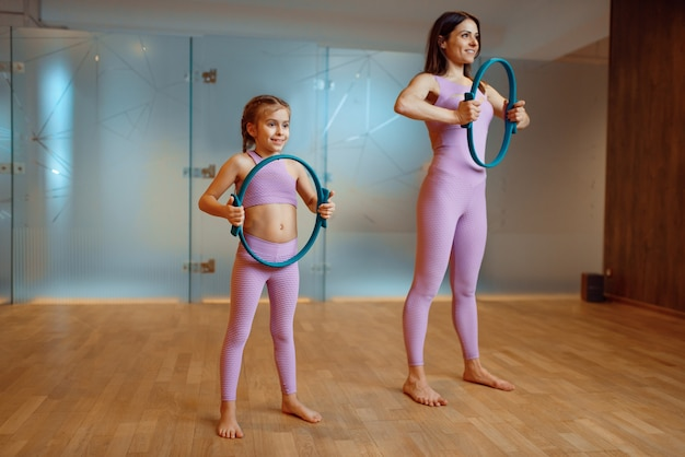 Mother and daughter in gym, pilates exercise with rings, yoga workout. mom and little girl in sportswear, woman with kid on joint training in sport club