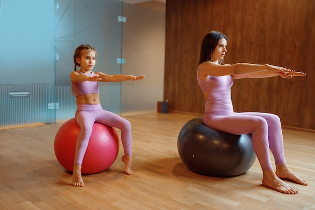 Mother and daughter in gym, pilates with balls, yoga workout. mom and little girl in sportswear, woman with kid on joint training in sport club