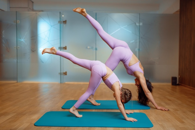 Mother and daughter in gym, stretching exercise in motion, yoga workout. mom and little girl in sportswear, woman with kid on joint training in sport club