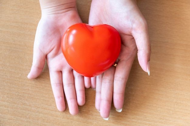 Mother and daughter hands holding red heart, health care, donate and family insurance concept