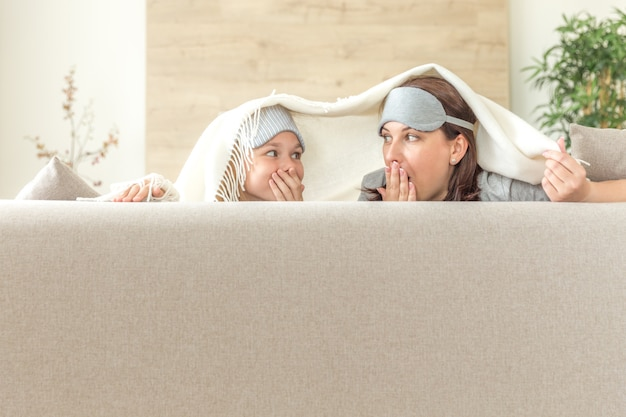 Mother and daughter happ family concept, wearing sleeping mask and having fun on sofa in living room