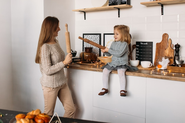 Mother and daughter happy family in the kitchen
