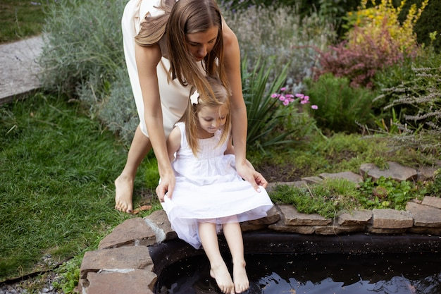 Mother and daughter having fun near pond in summer