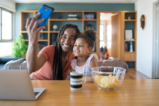 Mother and daughter having fun together and taking a selfie with mobile phone while staying at home. monoparental concept. new normal lifestyle concept.