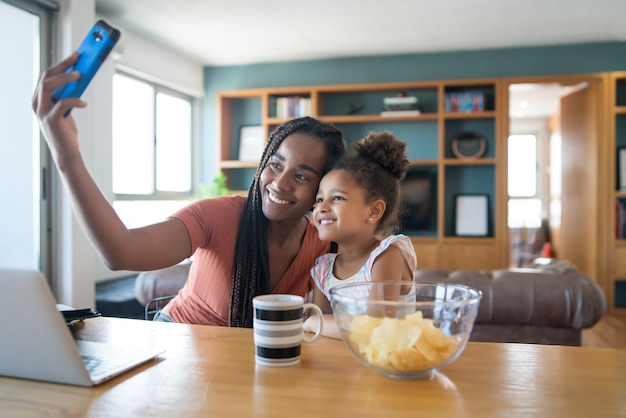 Mother and daughter having fun together and taking a selfie with mobile phone while staying at home. monoparental concept.