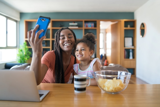 Mother and daughter having fun together and taking a selfie with mobile phone while staying at home. monoparental concept