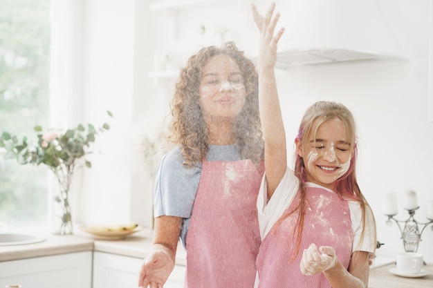 Mother and daughter having fun while cooking dough in kitchen