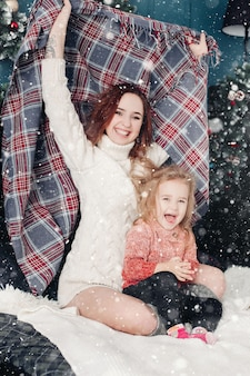 Mother and daughter having fun with blanket