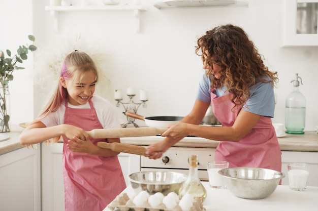 Mother and daughter having fun with rolling pins in kitchen while cooking