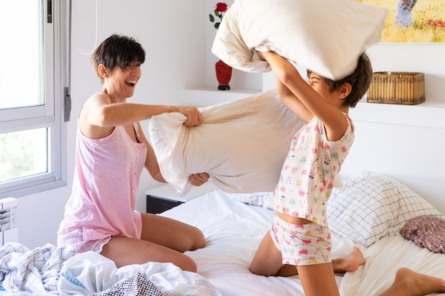 Mother and daughter having funny pillow fight on bed.