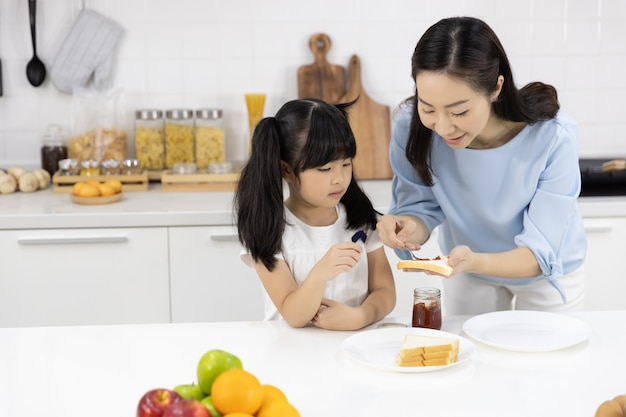 Mother and daughter helped to make breakfast in the kitchen at home