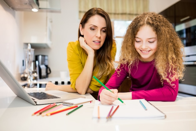 Mother and daughter helping daughter with her homework