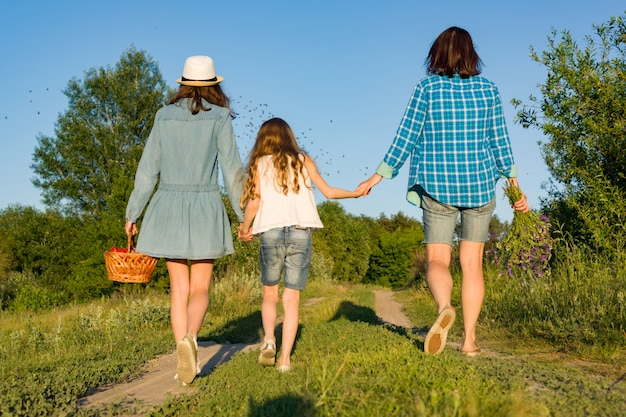 Mother and daughter hold hands, walk along the country road.