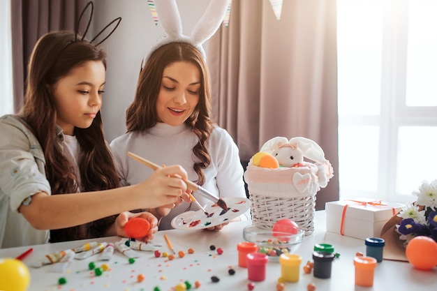 Mother and daughter hold paintbrushes and get some color for eggs