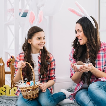 Mother and daughter holding easter eggs in hand looking at each other
