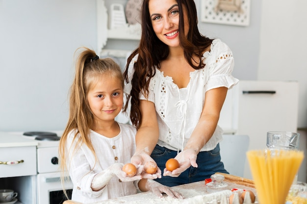 Mother and daughter holding eggs