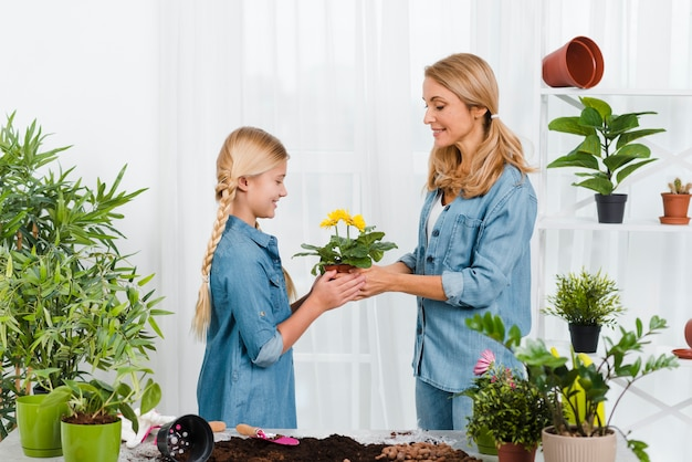Mother and daughter holding flower pot