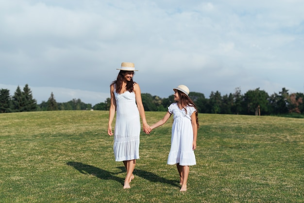 Mother and daughter holding hands outdoors