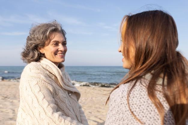 Madre e figlia che si tengono per mano insieme alla spiaggia