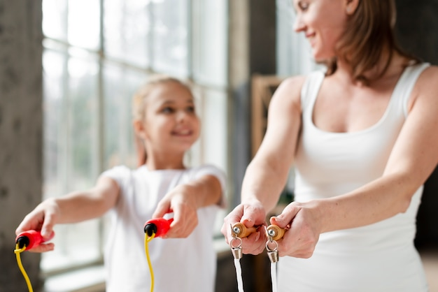 Mother and daughter holding jump ropes