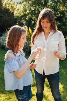 Mother and daughter holding marshmallow skewer in garden