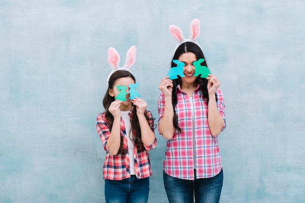 Mother and daughter holding paper cutout bunny in front of eyes against blue wall