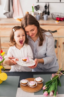 Mother and daughter holding plate with cupcake