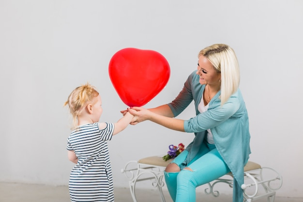 Mother and daughter holding red heart balloon