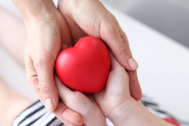 Mother and daughter holding red toy heart closeup