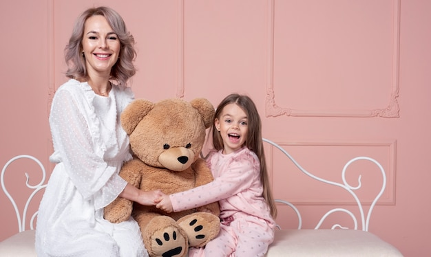 Mother and daughter holding teddy bear