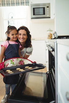 Mother and daughter holding tray of baked cookies in kitchen