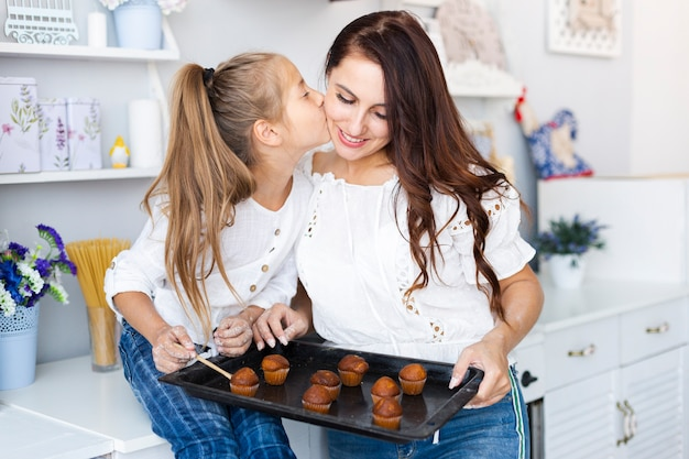 Mother and daughter holding  a tray with muffins