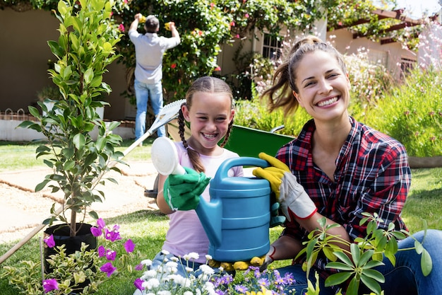 Mother and daughter holding a watering can while gardening