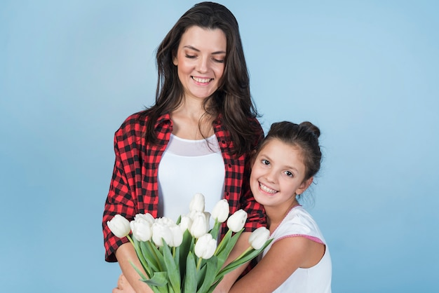 Mother and daughter holding white tulips